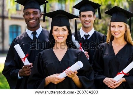 Feeling confident in their future. Four college graduates in graduation gowns standing close to each other and smiling - stock photo