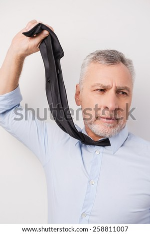 Feeling despair. Frustrated senior man in shirt stretching his necktie while standing against white background - stock photo