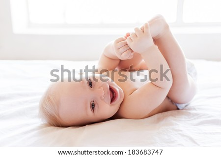 Feeling dry and happy. Happy little baby smiling while lying in bed - stock photo