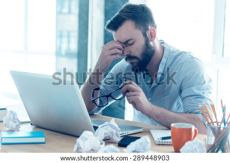 Feeling exhausted. Frustrated young beard man massaging his nose and keeping eyes closed while sitting at his working place in office  - stock photo