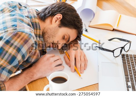 Feeling exhausted. Top view of young man sleeping while sitting at his working place - stock photo