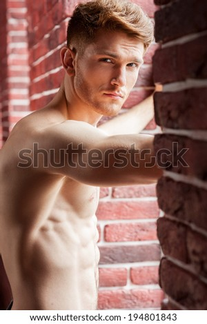 Feeling flirty. Handsome young shirtless man looking at camera while standing in front of the window - stock photo