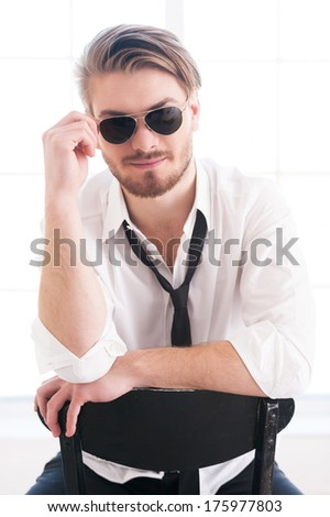 Feeling flirty. Thoughtful young man adjusting his sunglasses and looking at camera while sitting on the chair - stock photo