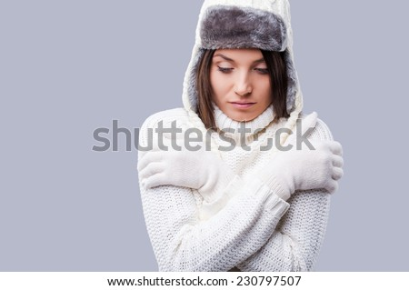 Feeling frosty. Frozen young women in winter clothing hugging self while standing against grey background - stock photo