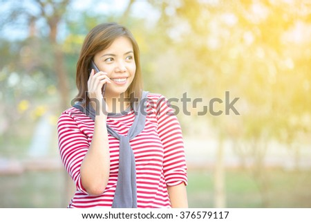 Feeling good and smiling young women talking with cell phone in park,warm light effect - stock photo