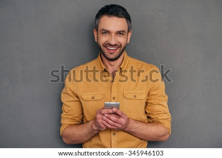 Feeling happy with his new smart phone. Handsome mature man holding smart phone and looking at camera with smile while standing against grey background - stock photo