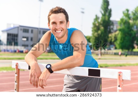 Feeling happy. Young smiling sportsman leaning on bar on stadium. - stock photo