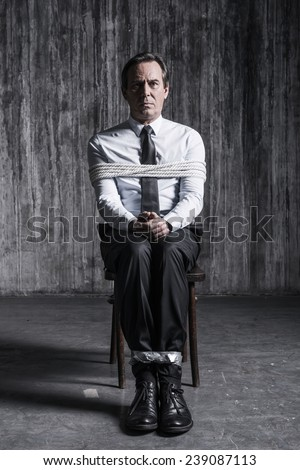 Feeling hopeless. Shocked businessman sitting at the chair and shouting while being tied up  - stock photo