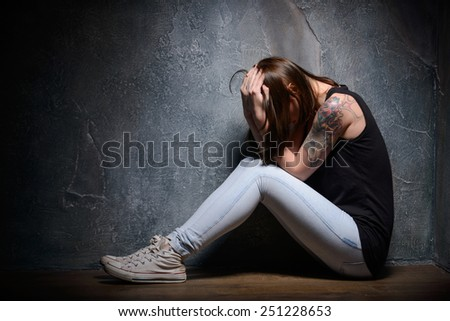 Feeling hopeless. Young woman trapped holding head in hands while sitting on the floor in a dark room - stock photo
