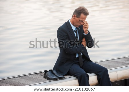 Feeling lonely and depressed. Depressed mature businessman touching his face with hand while sitting barefoot at the quayside  - stock photo