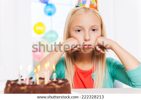 Feeling lonely at her party. Happy little girl looking at the birthday cake and smiling - stock photo