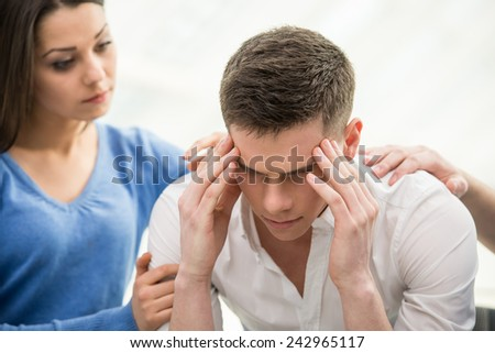 Feeling pain and depression. Depressed young man is sitting at the chair while woman is comforting his. - stock photo