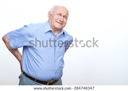 Feeling pain. Exhausted grandfather leaning frontways and touching his back with hands  - stock photo