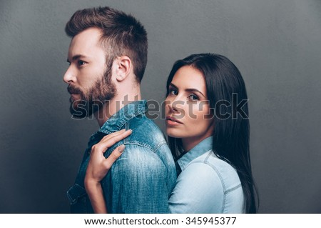 Feeling protected near him. Side view of beautiful young woman bonding to back of handsome beard man and looking at camera while both standing against grey background  - stock photo