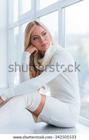 Feeling sad and lonely. Thoughtful young woman in white sweater and socks looking through a window while sitting on the floor at home  - stock photo