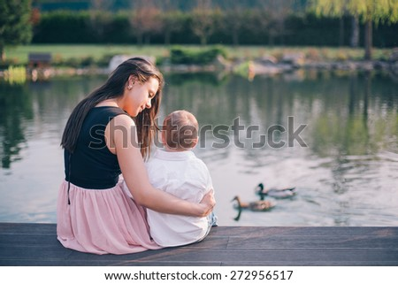 Feeling safe in mothers arms. Close-up of loving family bonding to each other while sitting on the pier - stock photo