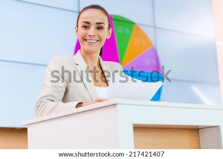 Feeling satisfied with her speech. Low angle view of confident young woman in formalwear standing at the tribune and smiling while making a presentation with projection screen in the background - stock photo