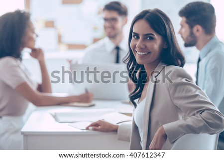 Feeling satisfied with her team. Beautiful cheerful woman looking at camera with smile while sitting at the office table with her coworkers - stock photo