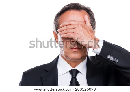 Feeling shame. Portrait of mature man in formalwear covering eyes with hand while standing against white background - stock photo