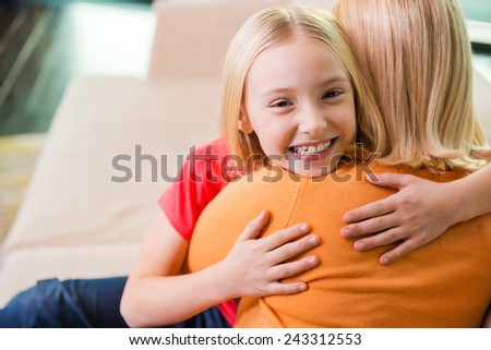 Feeling so happy near mom. Happy mother and daughter hugging while sitting on the couch together  - stock photo