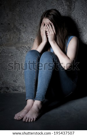 Feeling terrified. Shocked young woman covering face with hands while sitting on the floor in a dark room - stock photo