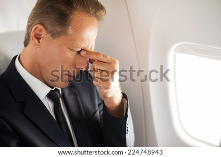 Feeling that awful headache. Frustrated mature businessman touching his face with hand and keeping eyes closed while sitting at his seat in airplane  - stock photo