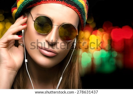 Feeling the Music. Close up Fashionable Young Woman Face, Wearing Rastafarian Hat and Trendy Round Sunglasses, Enjoying Party Music Through Headphone. Party Girl Portrait on Abstract Bokeh Background - stock photo