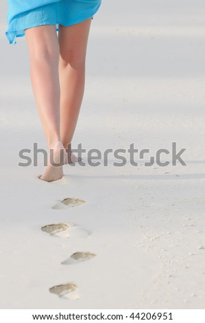 Feet and legs of woman walking on beach in warm early evening light. - stock photo