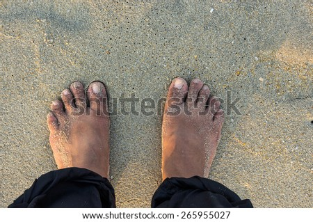feet are standing on the sandy beach during sunset - stock photo