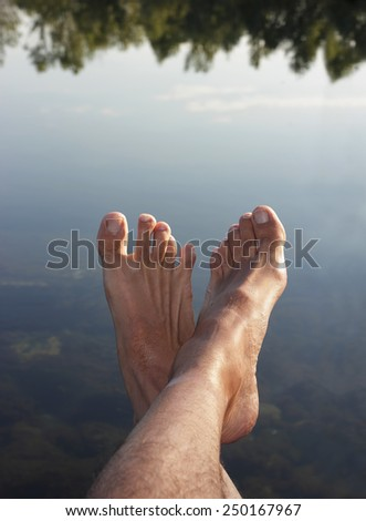 feet close up over a reflecting pool - stock photo