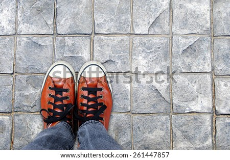 Feet in leather sneaker on pavement background, top view - stock photo