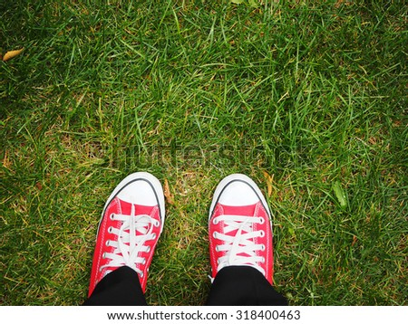 Feet in red sneakers on green grass, top view, informal style - stock photo