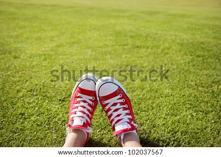 Feet in sneakers in green grass - stock photo