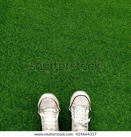 Feet in white sneakers on green grass, top view, informal style great for any use. - stock photo