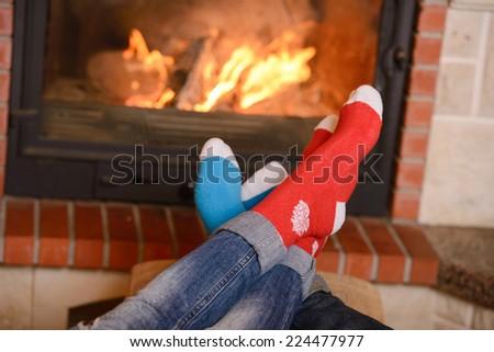 Feet in wool socks warming by cozy fire - stock photo