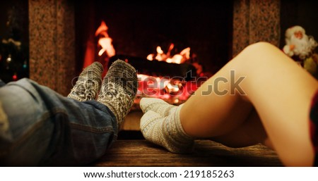 Feet in woolen socks warming by cozy fire in Christmas time in slow motion. Family couple warming their feet by the fireplace in winter time. - stock photo