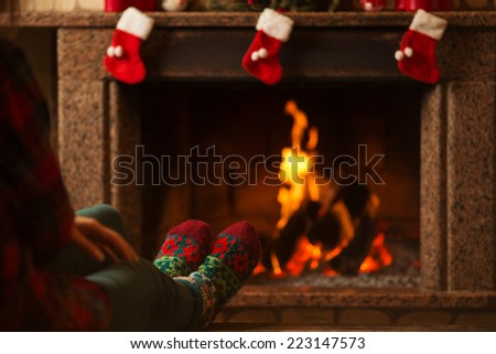 Feet in woollen socks by the Christmas fireplace. Woman relaxes by warm fire and warming up her feet in woollen socks. Close up on feet. Winter and Christmas holidays concept.  - stock photo