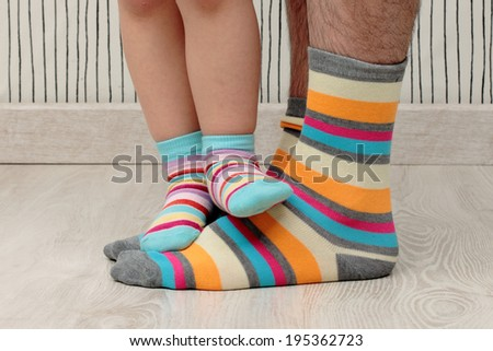 feet of a beautiful father and daughter with striped socks - stock photo