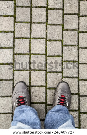 Feet of a man with jeans and shoes on the pavement, Selfie image - stock photo