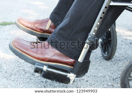 Feet of a person in a wheelchair - stock photo