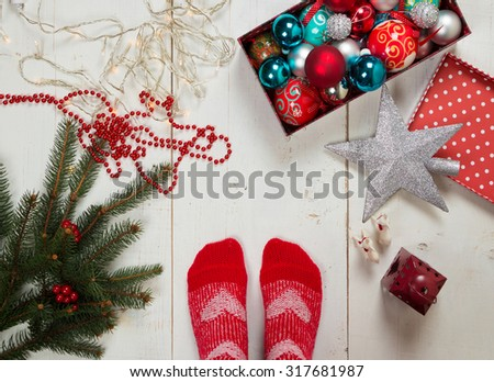 Feet of a person with red socks ready for decorating the Christmas tree surrounded by various ornaments on the floor - stock photo