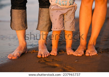 feet of a young family on a sea beach. Feet of mother, the father and the child stand on sand at sunset - stock photo