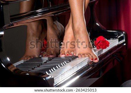 feet of a young girl on a piano keyboard with red rose - stock photo