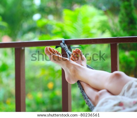 Feet of a young woman lying in hammock in a garden - stock photo