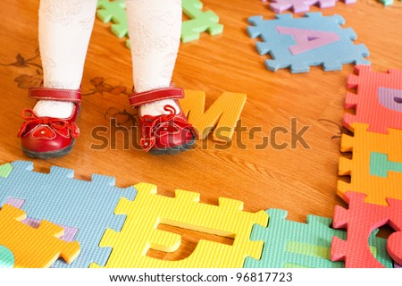 Feet of baby on the floor with puzzles - stock photo