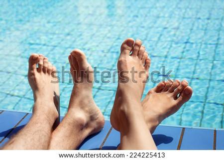 feet of couple near swimming pool - stock photo