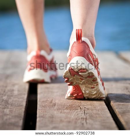 Feet of jogging person on wooden bridge - stock photo