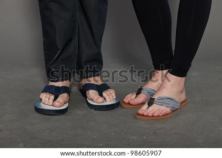 Feet of man and woman wearing flip-flops isolated on grey background. - stock photo
