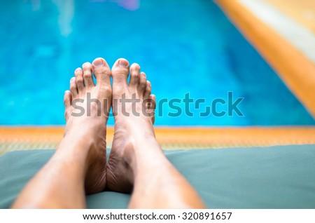 Feet of man laying beside swimming pool - stock photo