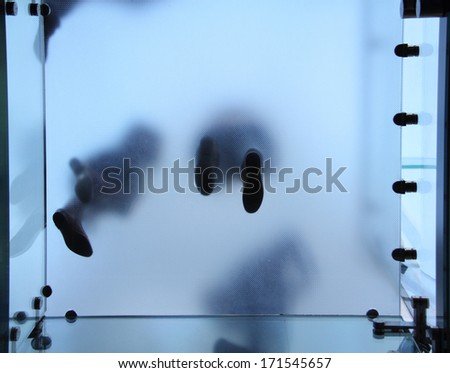 Feet of people who standing on translucent glass - stock photo